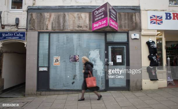 A woman passes the window of aN empty shop in the town centre of Yeovil on February 2 2017 in Somerset England Business rates which are based on the...