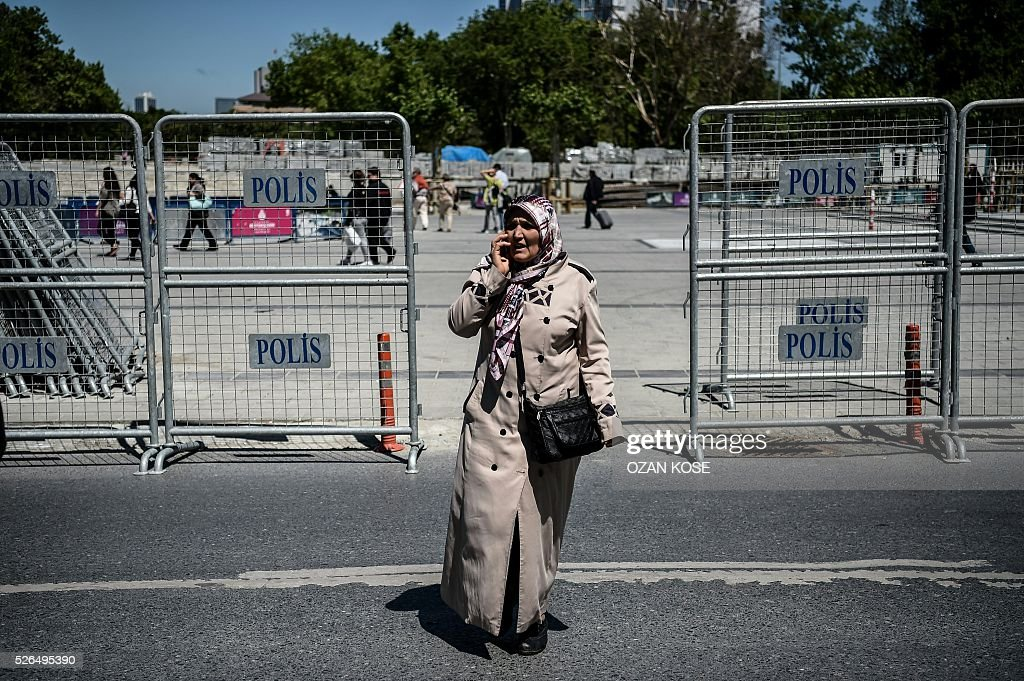 A woman passes through police barriers on the Taksim square, April 30, 2016 in Istanbul. Istanbul braced for a major security lockdown for May Day on Sunday, with almost 25,000 police on duty and numerous roads closed for an occasion that regularly sees clashes between Turkish protesters and police. / AFP / OZAN