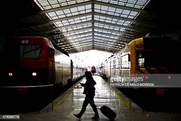 A woman passes two trains at Santa Apolonia train station in Lisbon on March 13 2014 REFER National Railways Company and CP Portugal Trains are on a...