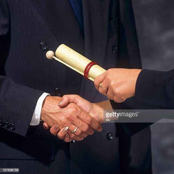 Woman passing an award document to a man