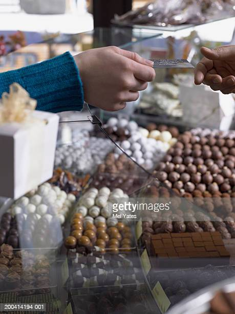 Woman passing bank card across counter in chocolate shop, close-up