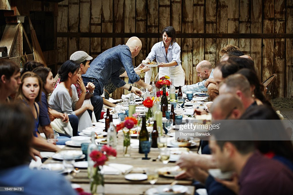 Woman passing food to friends and family : Stock Photo