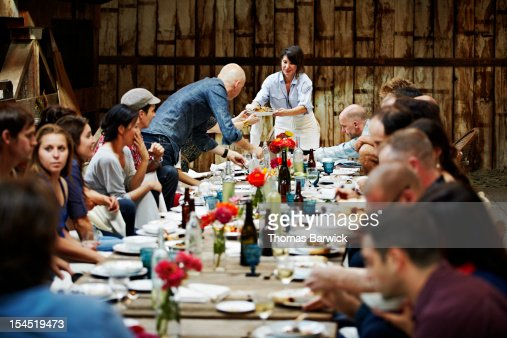 Woman passing food to friends and family
