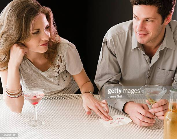 Woman passing her phone number to man at bar