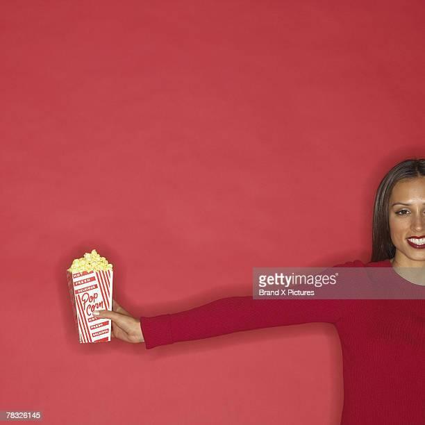 Woman passing popcorn