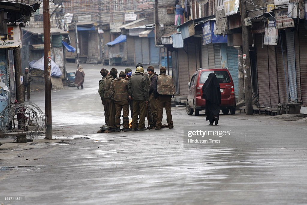 A woman past policemen during curfew in entire valley to thwart the 'Eid-Gah challo' call given by separatist's parties on February 15, 2013 in Srinagar, India. Most of the valley is reeling under strict curfew and all roads coming to summer capital has been blocked with concertina wires and road blockades.