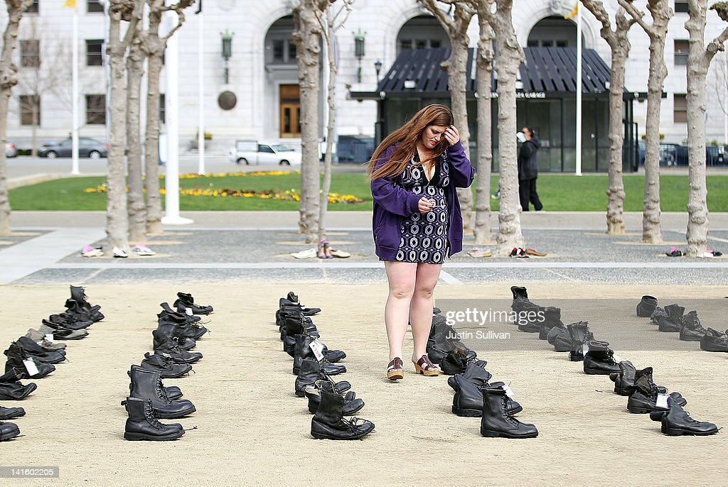 A woman pauses as she looks at rows of combat boots that are part of the 'Eyes Wide Open' exhibit in front of San Francisco City Hall on March 19, 2012 in San Francisco, California. The Eyes Wide Open exhibition includes a pair of boots for every one of the 481 California servicemen and women who died in the Iraq war.