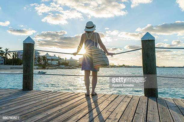 Woman pauses besides rope rail, looks to sea