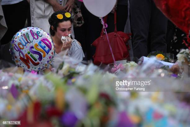 A woman pauses for thought as she looks at floral tributes and messages in St Anns Square on May 24 2017 in Manchester England on May 24 2017 in...