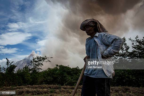 A woman pauses her work as Mount Sinabung spews pyroclastic smoke seen from Simpang Empat village on June 19 2015 in Karo District North Sumatra...
