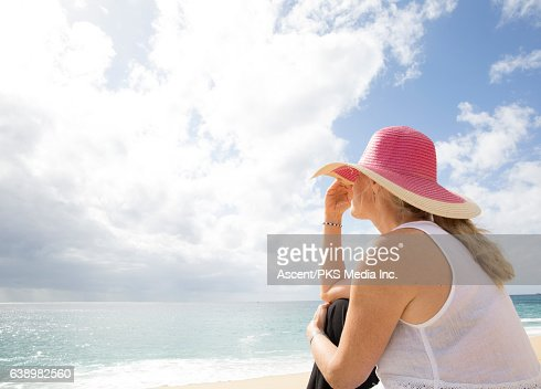 Woman pauses near water's edge, looks out to sea