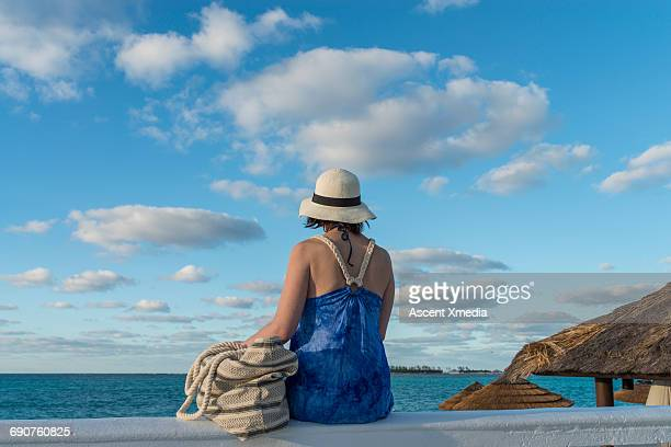 Woman pauses on rail, looks out to sea