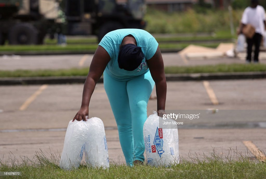 A woman pauses while carrying bags ice from an aid distribution center for victims of Hurricane Isaac on August 31, 2012 in New Orleans, Louisiana. The center was one of three in New Orleans operated by the Louisiana National Guard, which handed out bags of ice, boxes of food and tarps to residents, many of whom still have no electricity due to the storm.