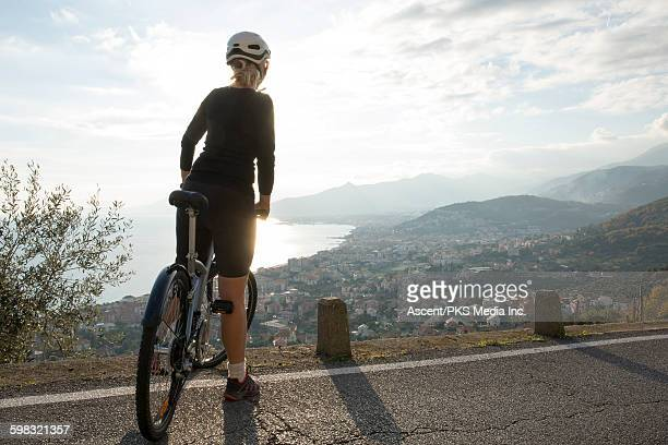Woman pauses with bike above village, sea