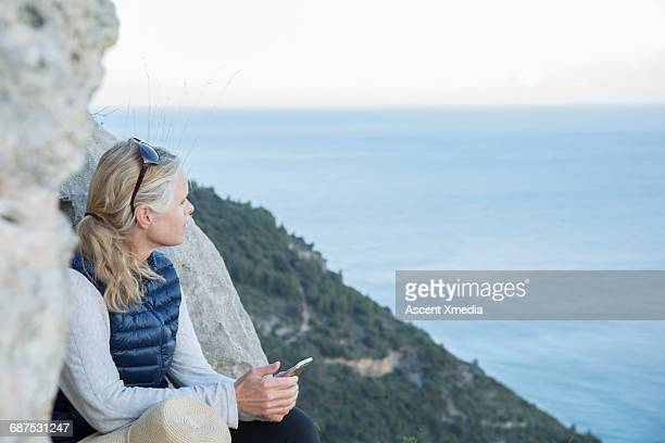 Woman pauses with smart phone at sea overlook