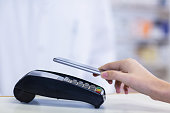 Woman paying bill through smartphone using NFC technology in pharmacy