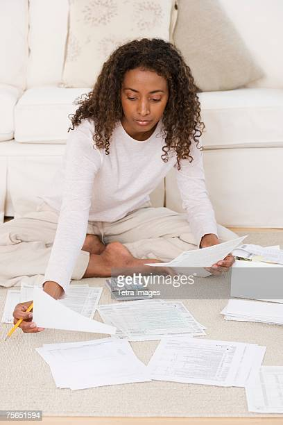 Woman paying bills on floor