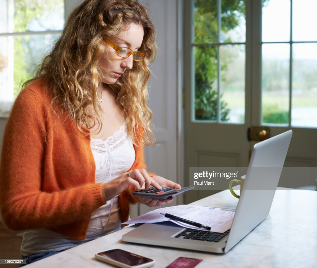 Woman paying bills on laptop : Stock Photo