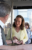 Woman paying bus fare to driver, smiling