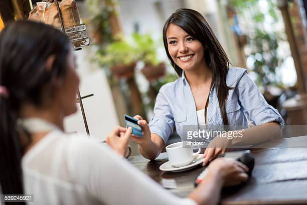 Woman paying by card at a cafe