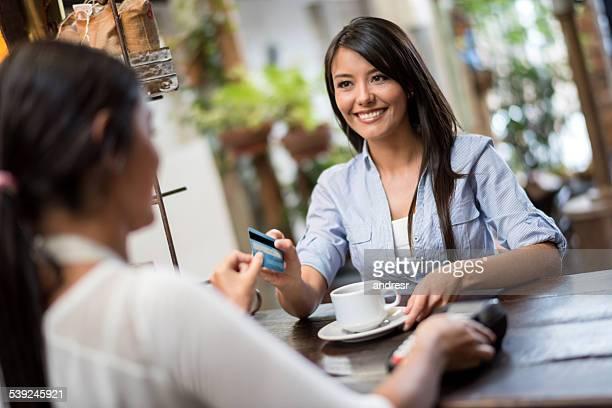 Mulher pagando pelo cartão em um café