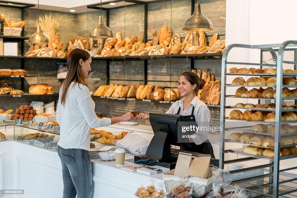 Frau bezahlen mit Kreditkarte an der Kasse des bakery  : Stock-Foto