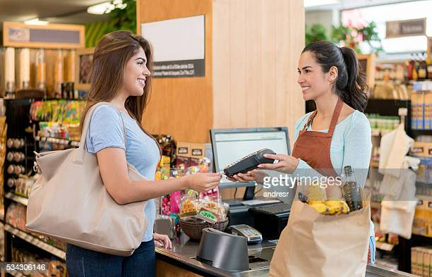 Woman paying by card at the grocery store