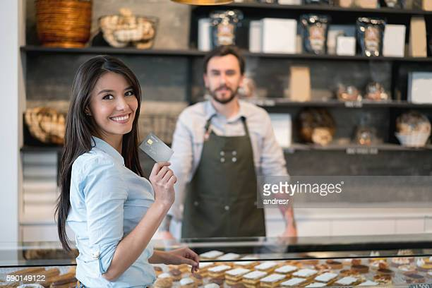 Woman paying by credit card at the bakery