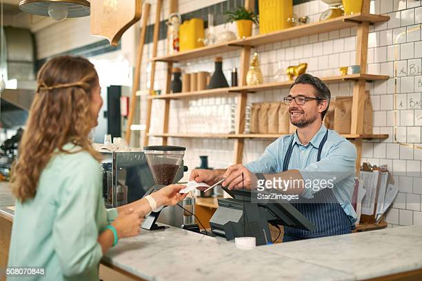 Woman paying for coffee with credit card at cafe