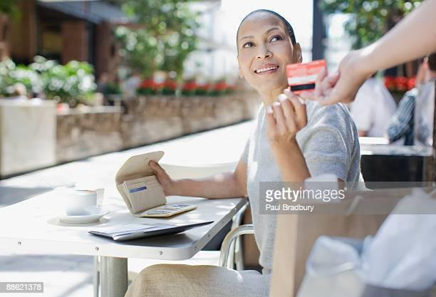 Femme payer pour un café avec votre carte de crédit