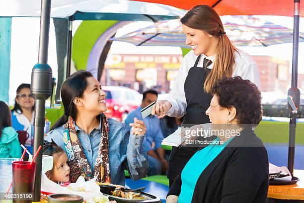 Femme de payer avec une carte de crédit pour repas au restaurant Tex-Mex