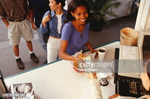 Woman paying for order in fast food restaurant