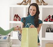 Woman paying for shopping in shoe shop