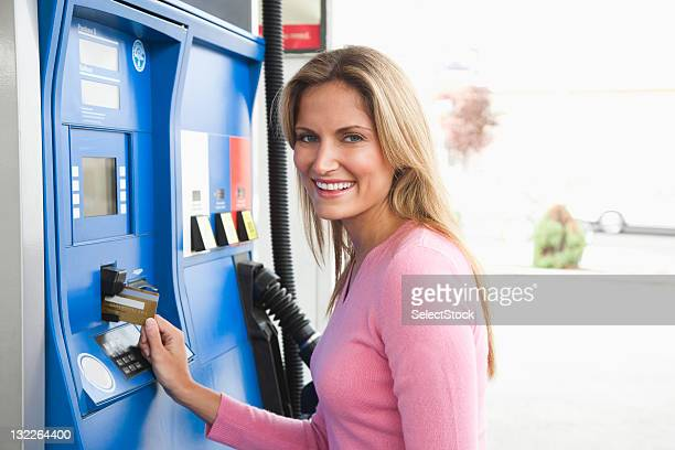 Woman paying gas pump with card