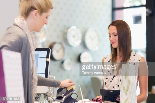 Woman paying in clothing store : Stock Photo