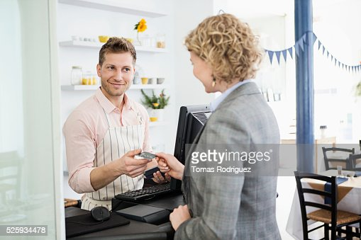 Woman paying with credit card at checkout counter in cafe : Stockfoto