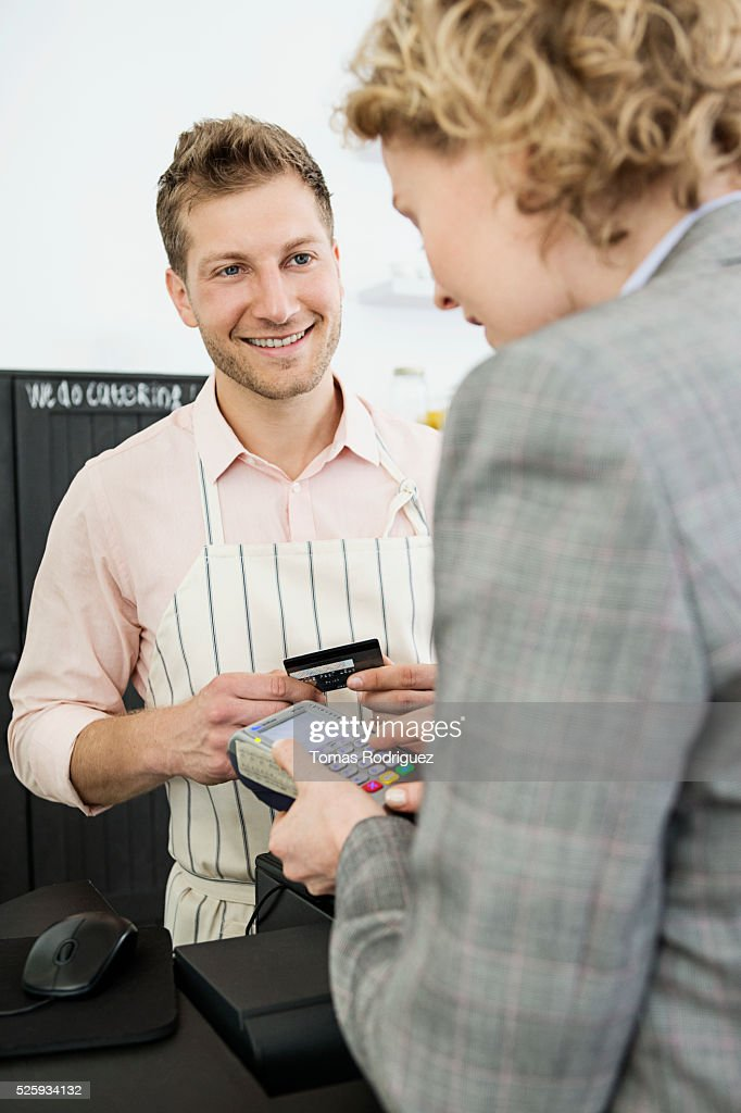 Woman paying with credit card at checkout counter : Stockfoto