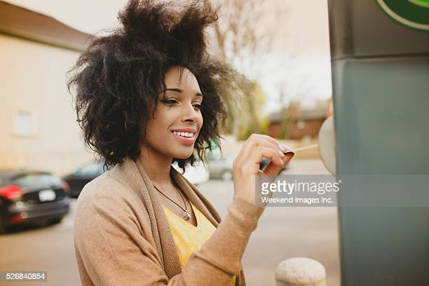 Woman paying with credit card on parking meter