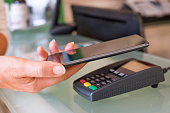 Female's hand using contactless smartphone to pay in a store