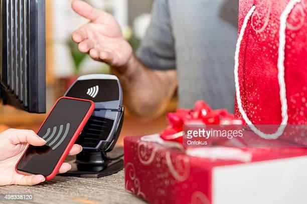 Femme payant avec technologie NFC sur le téléphone intelligent en magasin
