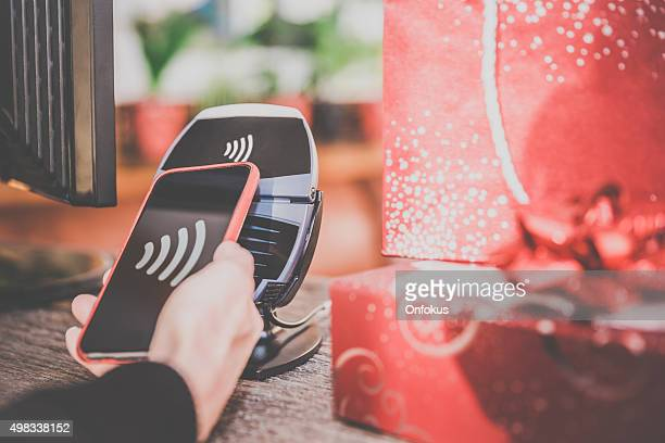 Woman Paying With NFC Technology on Smart Phone in Store
