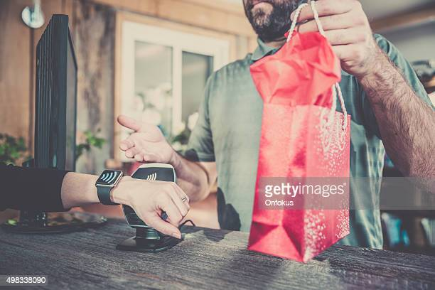 Woman Paying With NFC Technology on Smart Watch in Store