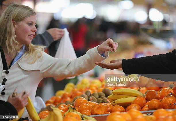 A woman pays a market vendor as he holds out his hand for fruit she purchased on July 23 2013 in Melbourne Australia As the 2013 Australian federal...