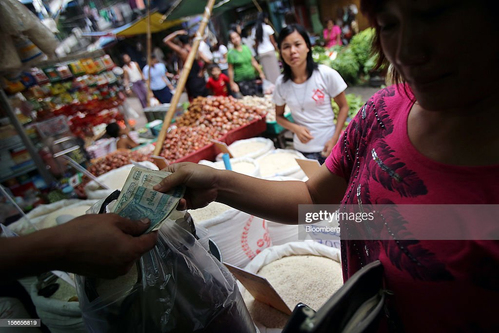 A woman pays as she shops for rice in at a market in Yangon, Myanmar, on Sunday, Nov. 18, 2012. President Barack Obama will become the first sitting U.S. president to visit Myanmar when he travels to Yangon on Nov. 19 to meet President Thein Sein and Aung San Suu Kyi, the opposition leader who spent more than 15 years under house arrest before the country shifted to democracy after decades of military rule. Photographer: Dario Pignatelli/Bloomberg via Getty Images