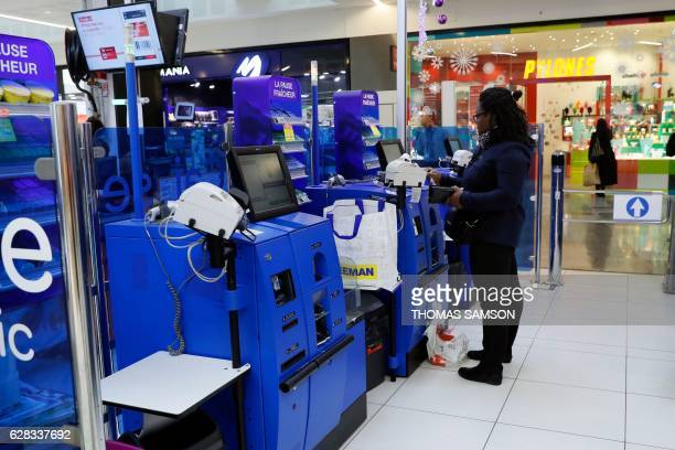 A woman pays at the selfcheckout machine at the exit of an hypermarket store of French retail giant Carrefour in VilleneuvelaGarenne near Paris on...
