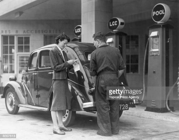 A woman pays for her petrol with a ration card at a petrol station in Wandsworth South London