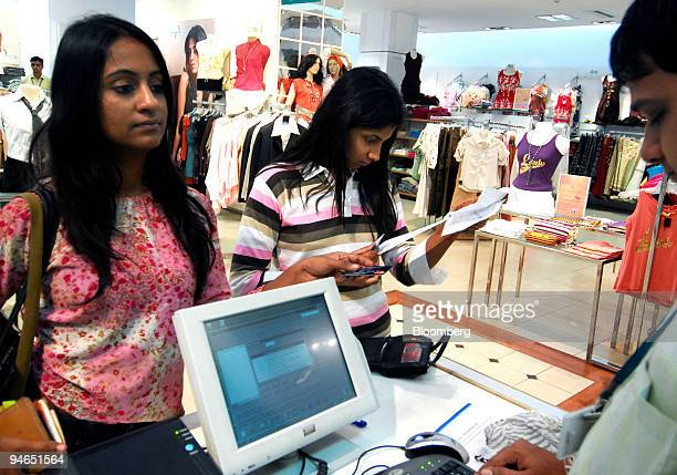 A woman pays for purchases at a mall in Mumbai India on Thursday Nov 29 2007 India's economy grew last quarter at the slowest pace since 2006...