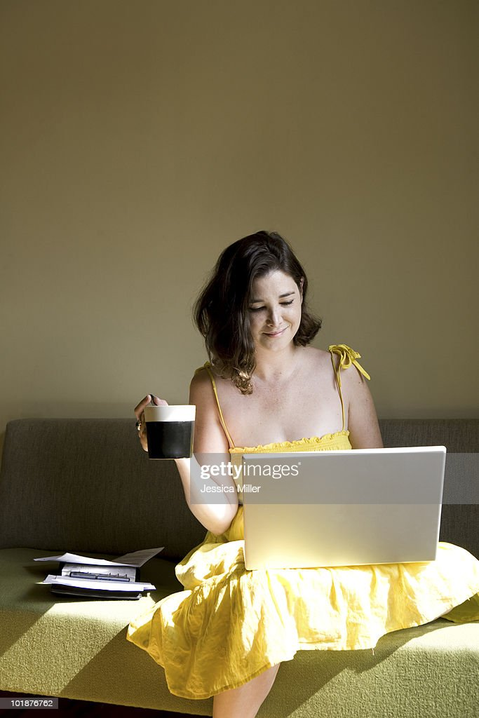 A woman pays her bills using online banking : Stock Photo