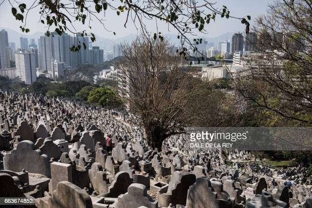 A woman pays her respects at a cemetery ahead of the Ching Ming Festival or gravesweeping day in Hong Kong on April 2 2017 Visiting the graves of...