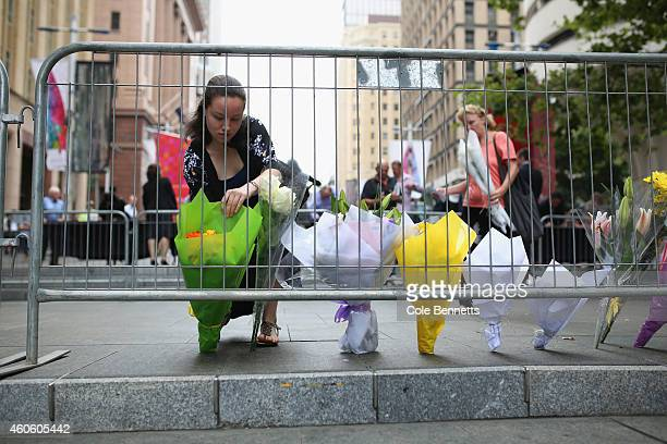 A woman pays her respects in a newly designated memorial area behind the main floral tribute on December 18 2014 in Sydney Australia Sydney siege...